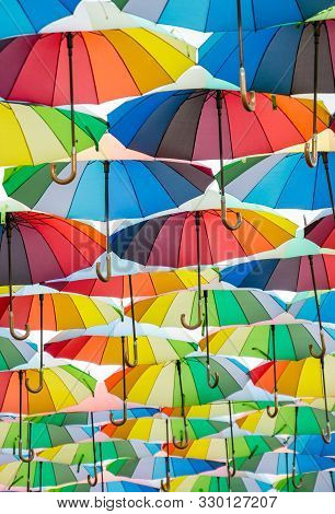 A Collection Of Open Umbrellas Floating In The Air, Each Umbrella Is Painted In All Colors Of The Ra