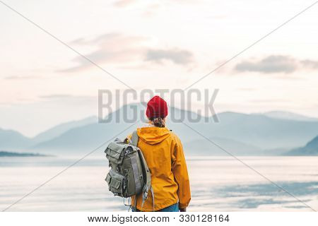 Back View Of Male Tourist With Rucksack Standing On Coast In Front Of Great Mountain While Journey.