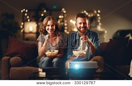 Family Couple Watching Television Projector At Home On The Sofa