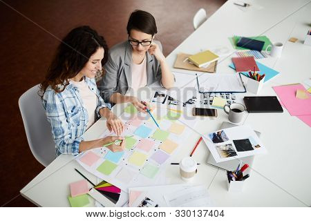 High Angle View At Two Young Businesswomen Creating Roadmap While Planning Design Project Sitting At