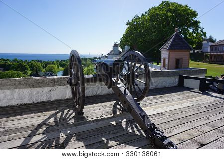 A Cannon Sits On A Platform At Fort Mackinac, On Mackinac Island, With A View Of The Mackinaw Strait