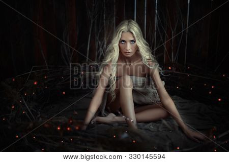 Charming Witch Woman With Blue Eyes And White Hair Sits In A Night Forest Among Red Lights. The Conc