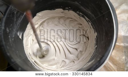Mixing White Putty. General Repair And Renovation. Home Improvement. Close-up. Worker Mixes A White