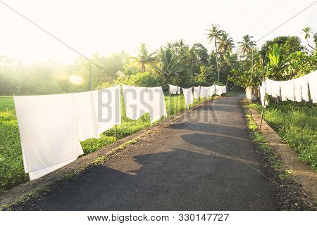 White Laundry On A Long Line Along A Street In A Tropical Forest With Sunset And Lens Flare, Alleppe