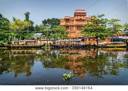 Alappuzha, India - 14 November 2017: Boats Along The Main Canal With Orange Hotel Building In The Do