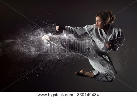 Energetic Strong Young Karate Girl Bounces And Makes A Kick And Hand Smashing Dust On A Gray Backgro