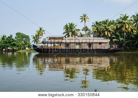 Traditional Houseboat In The Kerala Backwaters Along Palm Tree Coastline At A Cloudless Sunny Day, A
