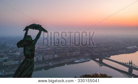 Aerial View To The Statue Of Liberty With Liberty Bridge And River Danube At Background Taken From G