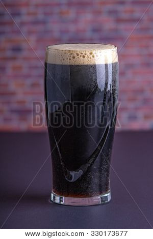 A Dark Irish Dry Stout Beer Glass That Originated In The Brewery In Dublin Vertical View