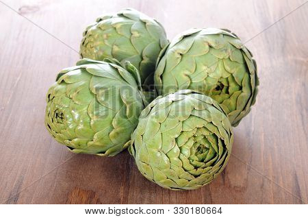 Four Of Artichoke On The Wooden Table