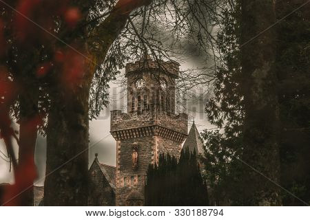 Fort Augustus, Scotland, December 17, 2018: The Abbey Highland Club Clock Tower, Across Leaves Of Tr