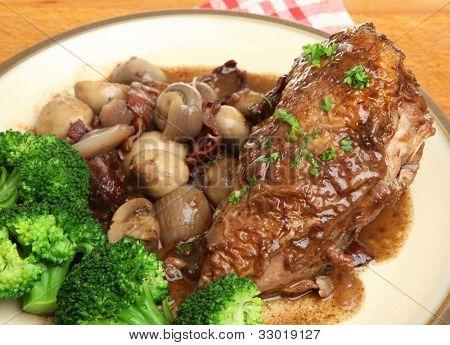 Coq au vin. Chicken casseroled in red wine. Focus on chicken breast.