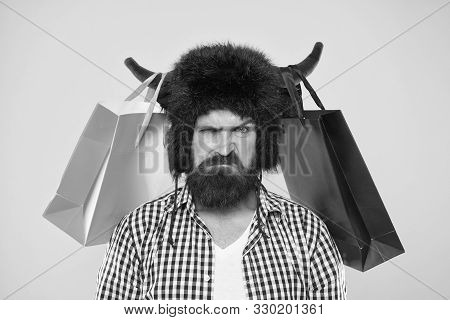 Dissatisfied With Purchase. Unhappy Hipster With His Purchase In Paperbags Hanging On Bull Horns. Br