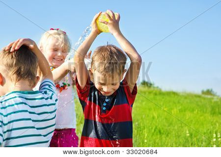 Excited kids spraying water on each other