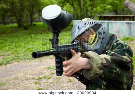 Paintball player in camouflage uniform and protective mask with traces of paintball hit aims with marker into enemies.