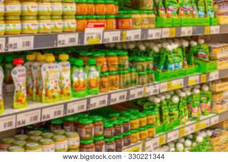 Defocused Background, Baby Food Supermarket Shelves, Fruit Puree And Porridge For Feeding Small Chil