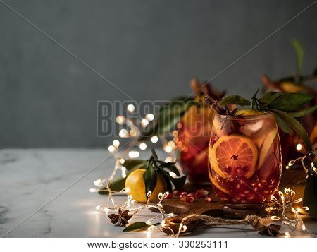 Winter Sangria On Dark Christmas Holiday Background. Jugful Of Sangria And Glasses With Fruit Slice,