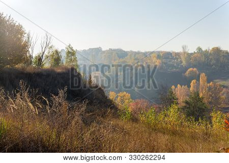 Valley Slopes With Gullies And Clay Cliff Overgrown With Trees And Grass In The Sun Backlight With M