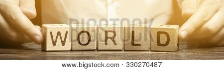 A Man Puts Wooden Blocks With The Word World. The Concept Of Globalization And Global Business. Inte