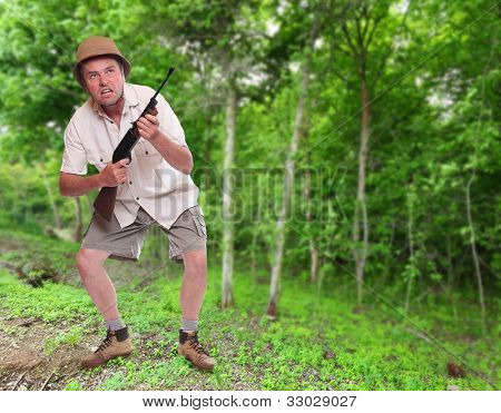 Funny picture of a crazy hunter with his hunting rifle in a tropical forest.