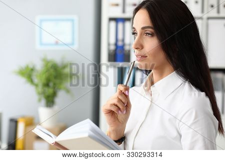Portrait Of Smart Businesswoman Overwhelmed With Thoughts Standing In Modern Office And Holding Pape