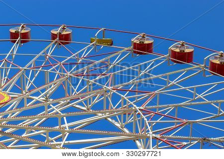 Big Ferris Wheel Moves. Bright Photo Of The Amusement Park. Red Cabins Against A Clear Blue Sky. Fer