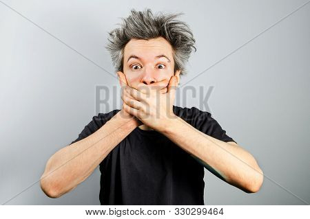Young White Caucasian Unshaven Guy With Long Gray Hair Close His Mouth And Silent On A Gray Backgrou