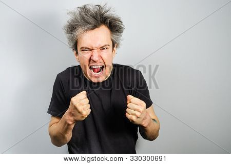 Young Aggressive White Caucasian Unshaven Guy With Long Hair Threatening Fists On A Gray Background
