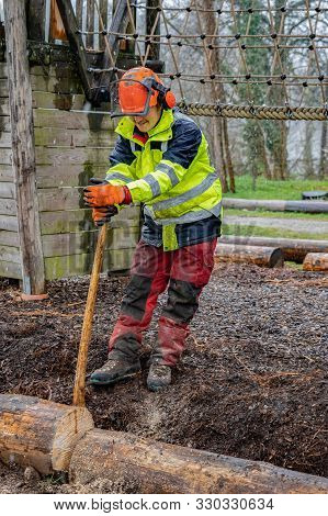 Young Loggers Working With An Ax On A Playground, Holding A Tree Trunk For Cutting It With A Chain S