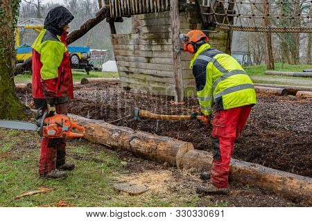 Young Loggers Working With An Ax On A Playground, Second Loggers Waiting With A Chain Saws After Cut