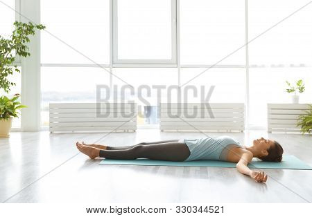 Young Woman Practicing Corpse Asana In Yoga Studio. Savasana Pose