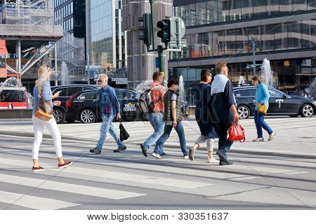 Stockholm, Sweden - September 10, 2019: People Crossing The Street At A Crosswalk Located At The Ser