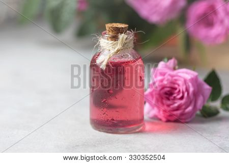 Natural Pure Rose Oil Or Scented Water In Bottles For Spa, Skin Care Or Aromatherapy. Glass Bottle O