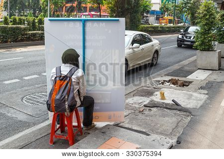 Bangkok, Thailand - 23rd March 2018: Man Sat On A Plastic Chair By The Side Of Sukhumvit Road Holdin
