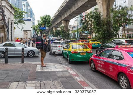 Bangkok, Thailand - 23rd March 2018: A Backpacker Waits For An Empty Taxi In Heavy Traffic On Sukhum