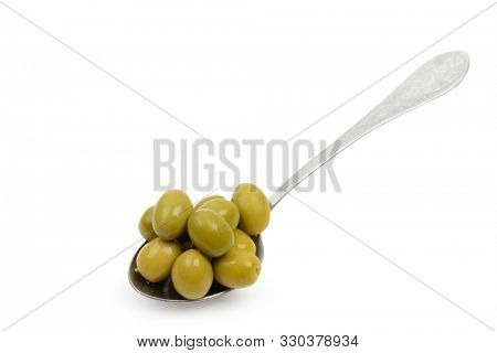 Spoon with wet green olives in brine isolated on white background with clipping path