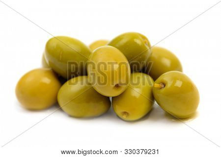 Pile of wet green olives macro in brine drops isolated on white background