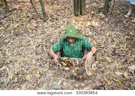 Tour Guide Demonstrating How A Vietcong Hide Into The Cu Chi Tunnels