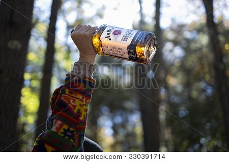 New York, Ny - October 19 2019: Woman Holding Up Bottle Of Jim Beam Bourbon Whiskey While Camping In