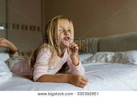 Cute Blonde Little Girl In Pajamas Playing In White Bed, Early Morning Before Going To Kindergarten.