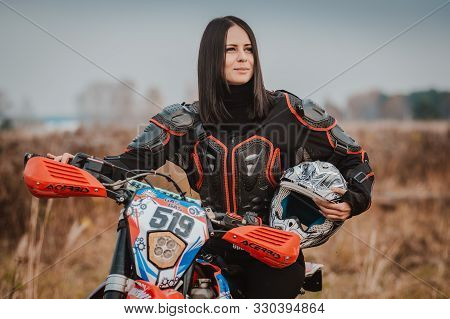 Beautiful Brunette Woman In Motorcycle Outfit. Female Motocross Racer Next To Her Motorcycle. Russia