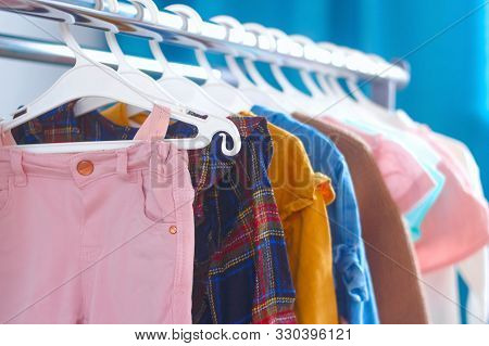 Pastel Color Children's Clothes In A Row On Open Hanger Indoors. Clothes For Little Ladies Hung In T