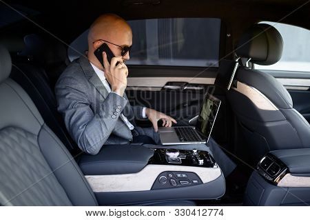 Handsome Businessman Using His Mobile Phone In A Modern Car With A Driver In Center Of The City. Con