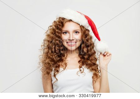 Happy Christmas Woman In Santa Hat Smiling On White Background. Christmas And New Year Party
