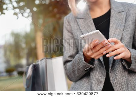 Close-up Of Woman Using Her Smartphone Outdoor In Park