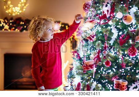 Child Decorating Christmas Tree. Kid On Xmas Eve.