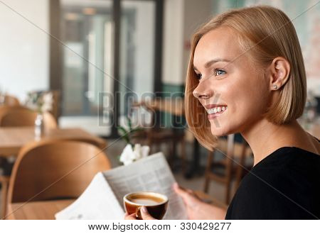 Young Blonde Woman Having A Breakfast With Coffee Reading Newspaper In Cafe.