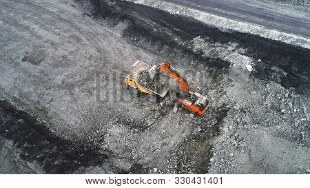 Coal Mining In A Quarry. A Hydraulic Excavator Loads A Dump Truck. The Process Of Loading Mining Tru