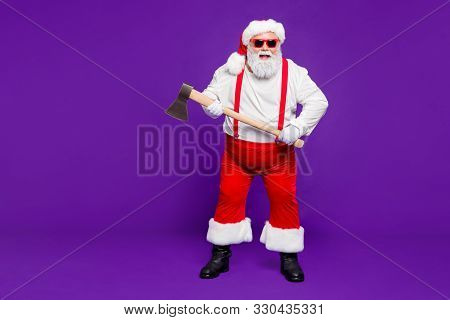 Full length body size view of his he nice funky hilarious cheery glad cheerful bearded thick fat dangerous Santa holding in hands ax isolated over bright vivid shine vibrant violet lilac background poster