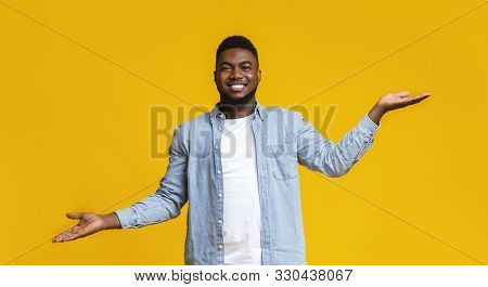 Make right choice. Handsome black man comparing variants, making scales with his empty hands over yellow studio background, panorama poster